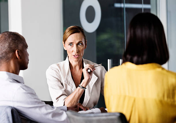 Angry businesswoman talking to colleagues stock photo