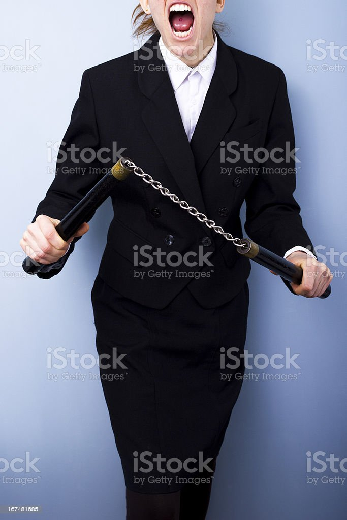 Angry businesswoman with nunchucks stock photo
