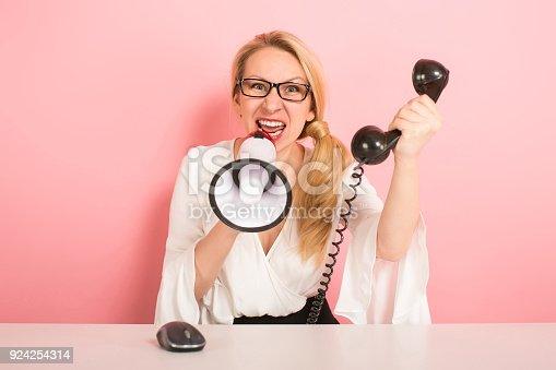 istock Angry businesswoman with phone and loudspeaker 924254314