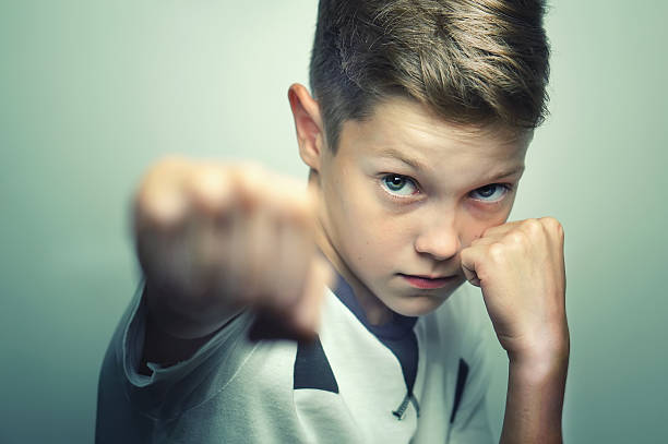 Angry child boy in white t-shirt training box punch. stock photo