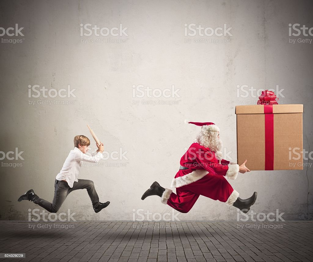 Angry child chasing Santa Claus stock photo