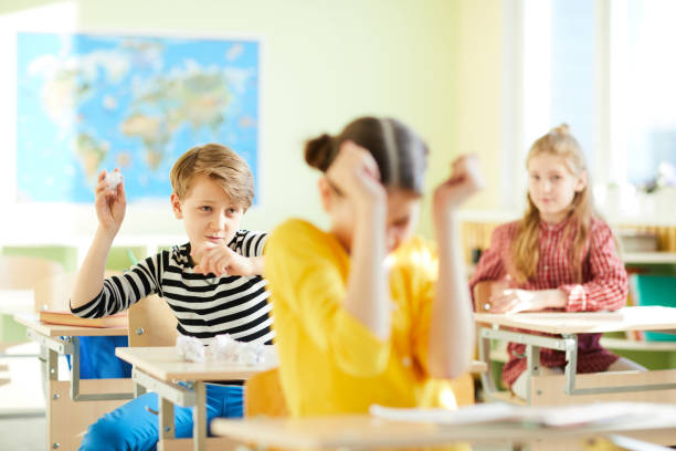 Angry children at school Angry school bully throwing paper ball at new girl and sitting at desk in geography classroom, bullying at school concept mischief stock pictures, royalty-free photos & images