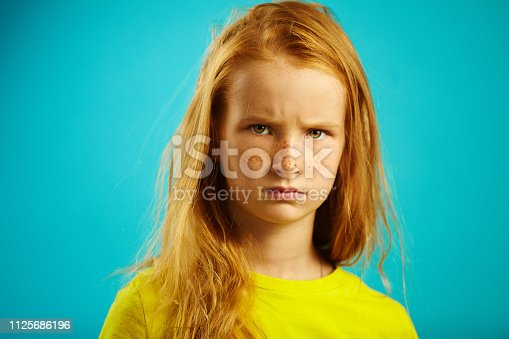 Angry children girl with red hair isolated on blue. Horizontal close-up image of unhappy child