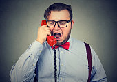 istock Angry chunky man talking on phone 910147876