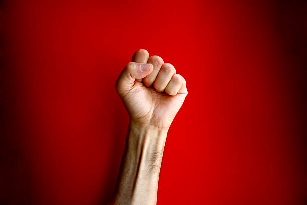 angry clenched fist on red background - fist stock photos and pictures