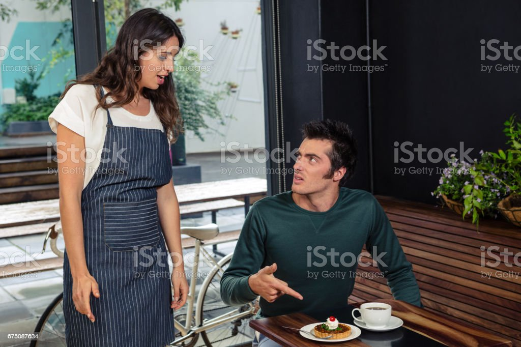 Angry client quarreling with waitress about wrong order stock photo