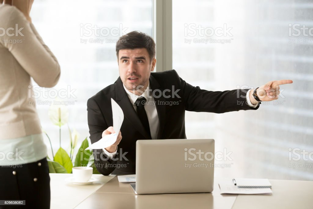 Angry company executive dismissing firing incompetent employee for paperwork error stock photo