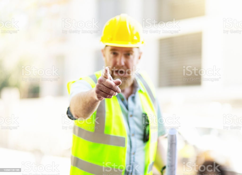 Angry construction worker in safety gear points accusingly stock photo