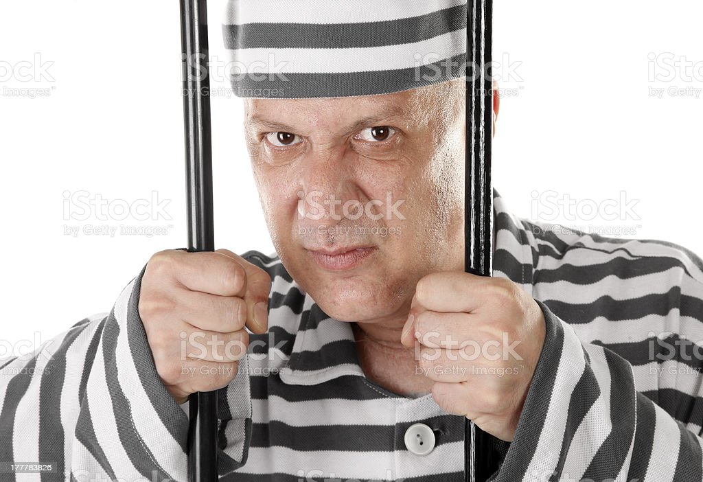 Angry convict prisoner jailbird behind bars stock photo