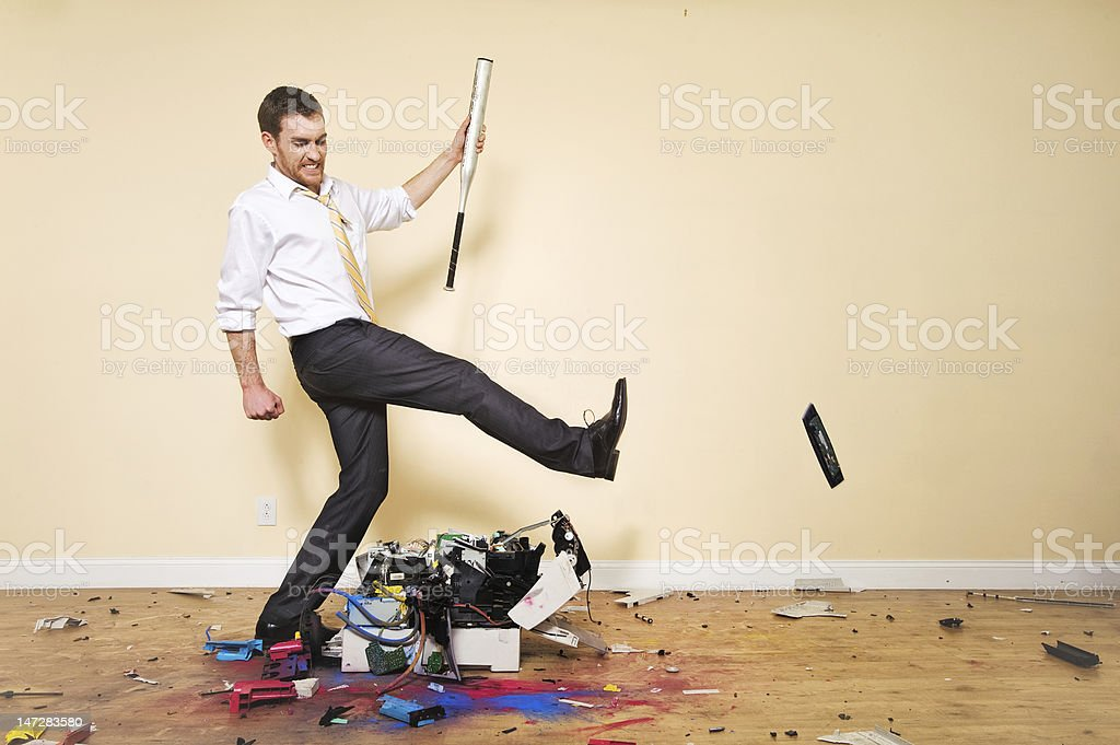 Angry Corporate Man Kicking Printer stock photo