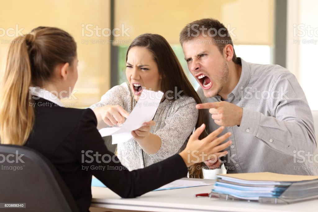 Angry couple claiming at office stock photo