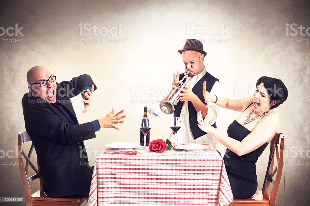 angry couple disturbed by a trumpet musician while having dinner series of different problems that can happen at dinner with your partner Acute Angle Stock Photo
