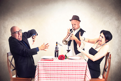 Angry Couple Disturbed By A Trumpet Musician While Having Dinner Stock Photo - Download Image Now