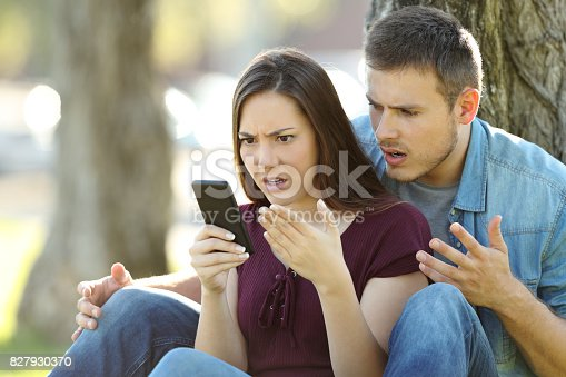 istock Angry couple using a smart phone outdoors 827930370