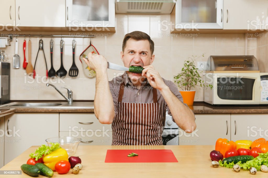 Angry crazy caucasian young man in apron, brown shirt sitting at table, attack cuts vegetable for salad with knife in light kitchen. Dieting concept. Healthy lifestyle. Cooking at home. Prepare food. stock photo