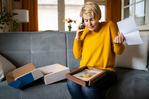 Angry confused woman sitting on the couch at home, looking at broken online store order is displeased by post shipping mistake and uses her phone to ring and complain