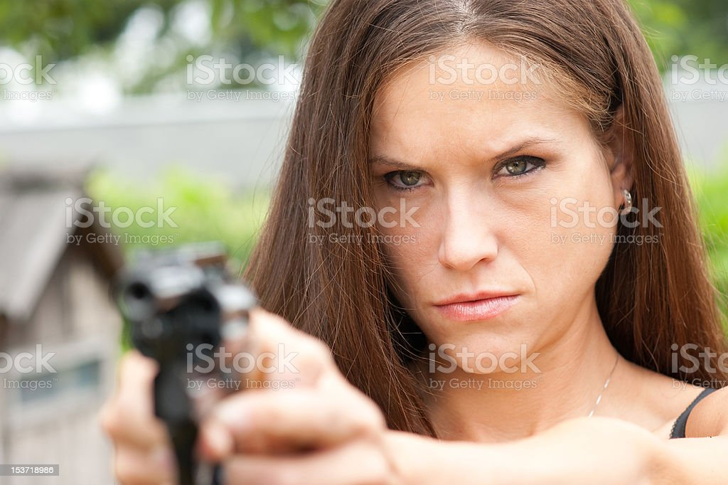 Angry Detective Girl Points Snub Nosed Hand Gun at Perpetrator stock photo