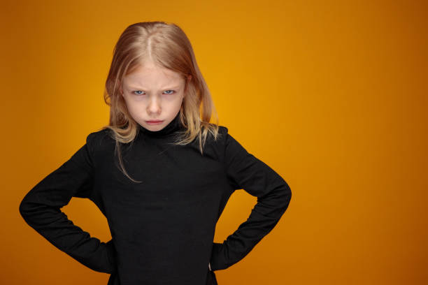 angry displeased little girl in black with long blond hair stock photo