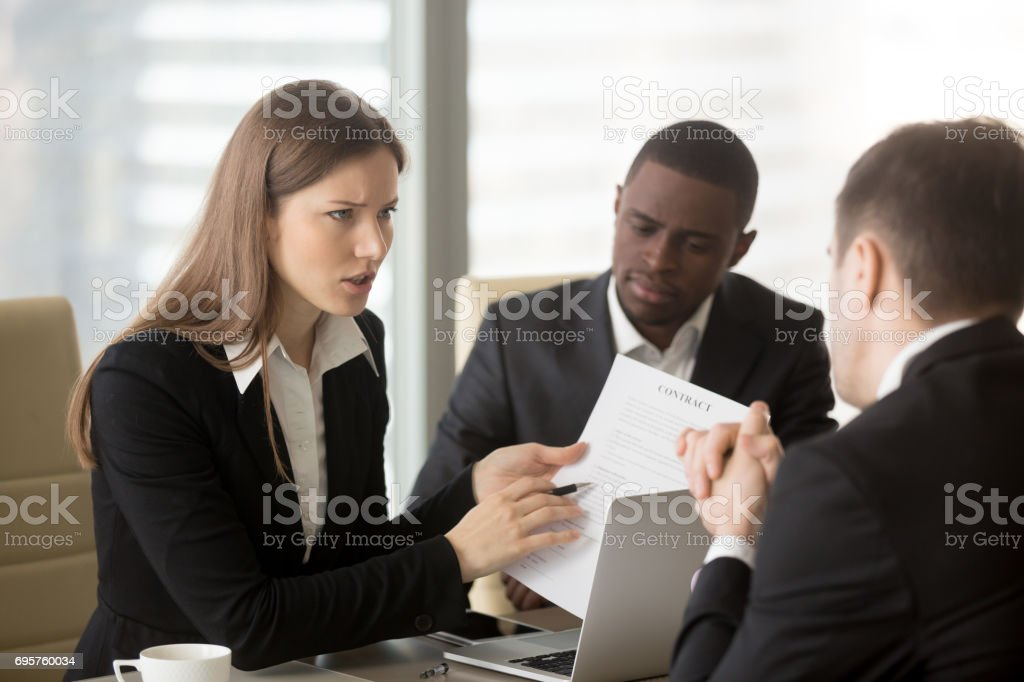 Angry dissatisfied businesswoman arguing with contractor, pointing at contract stock photo