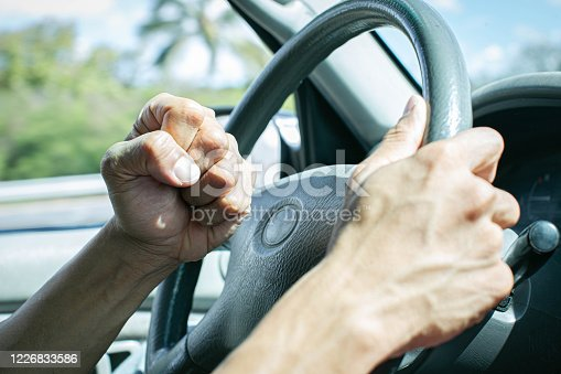 A man behind the steering wheel angry at other drivers banging on his horn in anger.