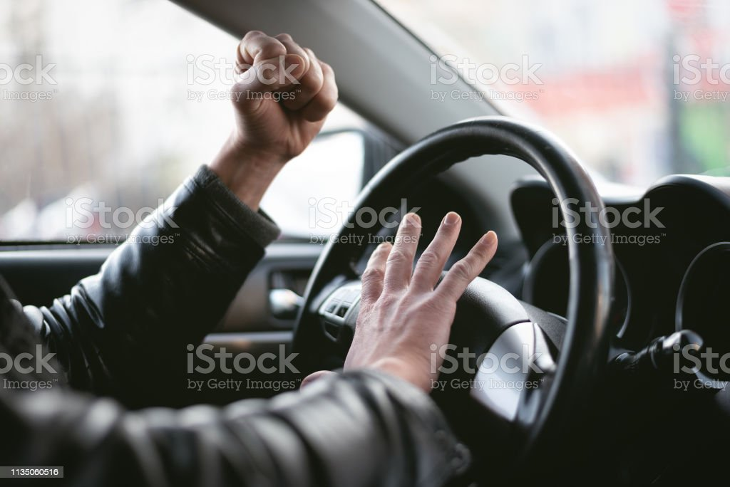 Angry driver. Angry driver is honking and is yelling by sitting of a steering wheel. Road aggression concept. Traffic jam. Abstract Stock Photo