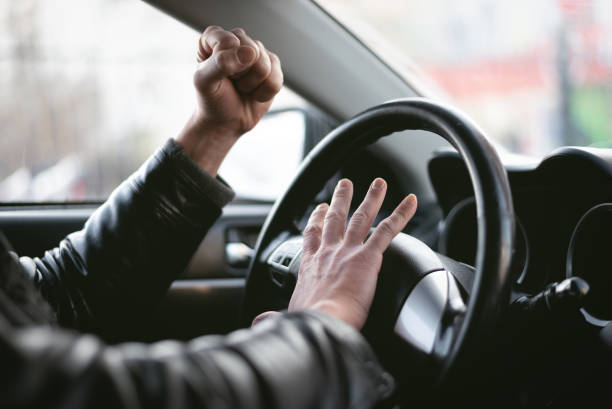 Angry driver. Angry driver is honking and is yelling by sitting of a steering wheel. Road aggression concept. Traffic jam. aggressively stock pictures, royalty-free photos & images
