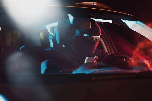istock Angry drunk driver sitting in car on the background of police car lighting 1128469563