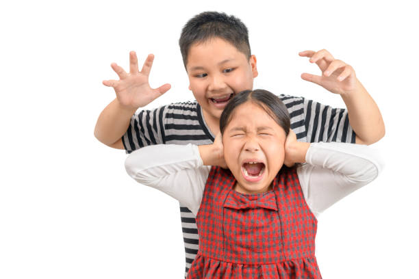 Angry elder brother attacks his sister isolated. stock photo