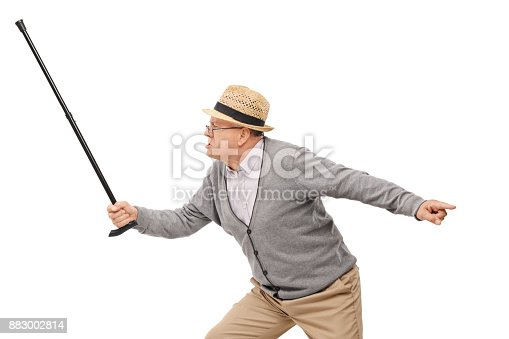 istock Angry elderly man holding a cane as a sword 883002814