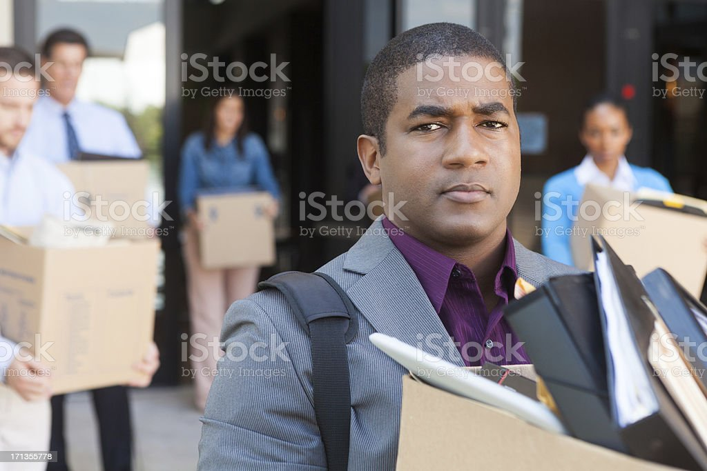 Angry employees leaving office building after being fired/ laid off stock photo