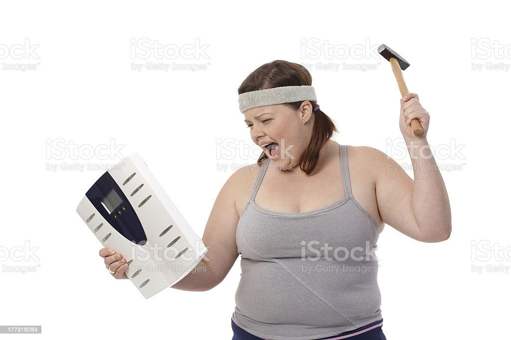 Angry fat woman with hammer and scale stock photo