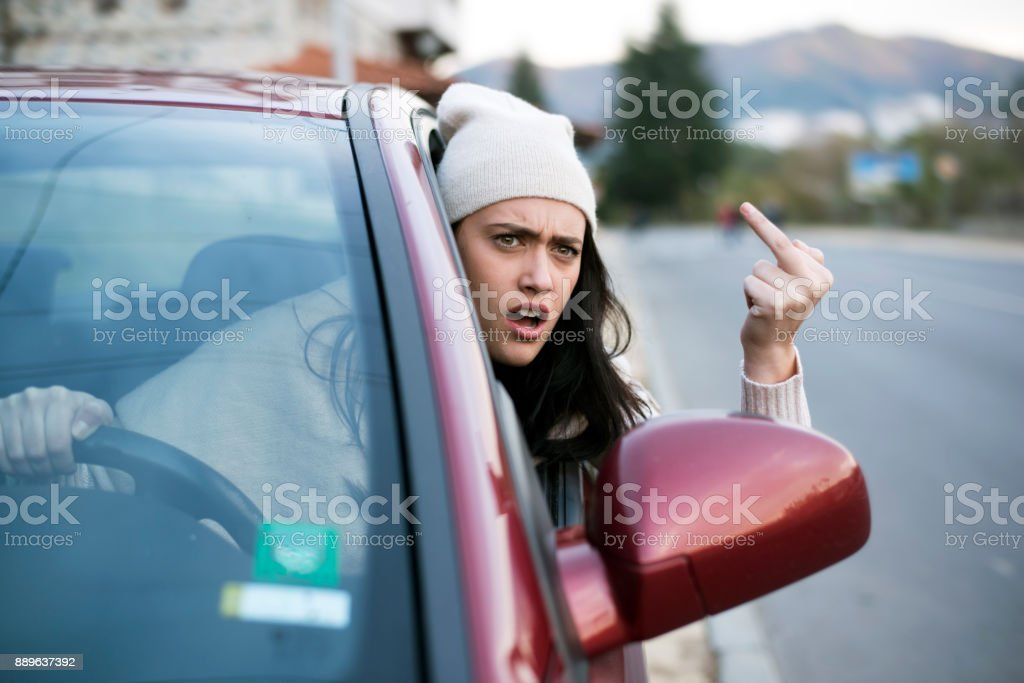 Angry female driver showing the finger stock photo