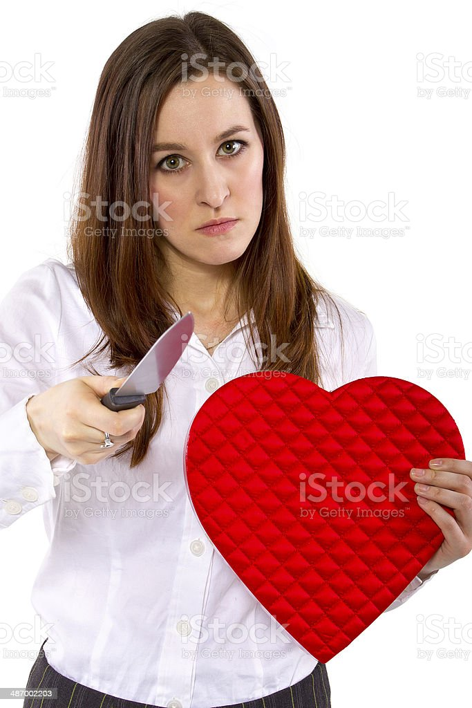Angry Female Ex-Lover Holding a Heart and a Knife stock photo