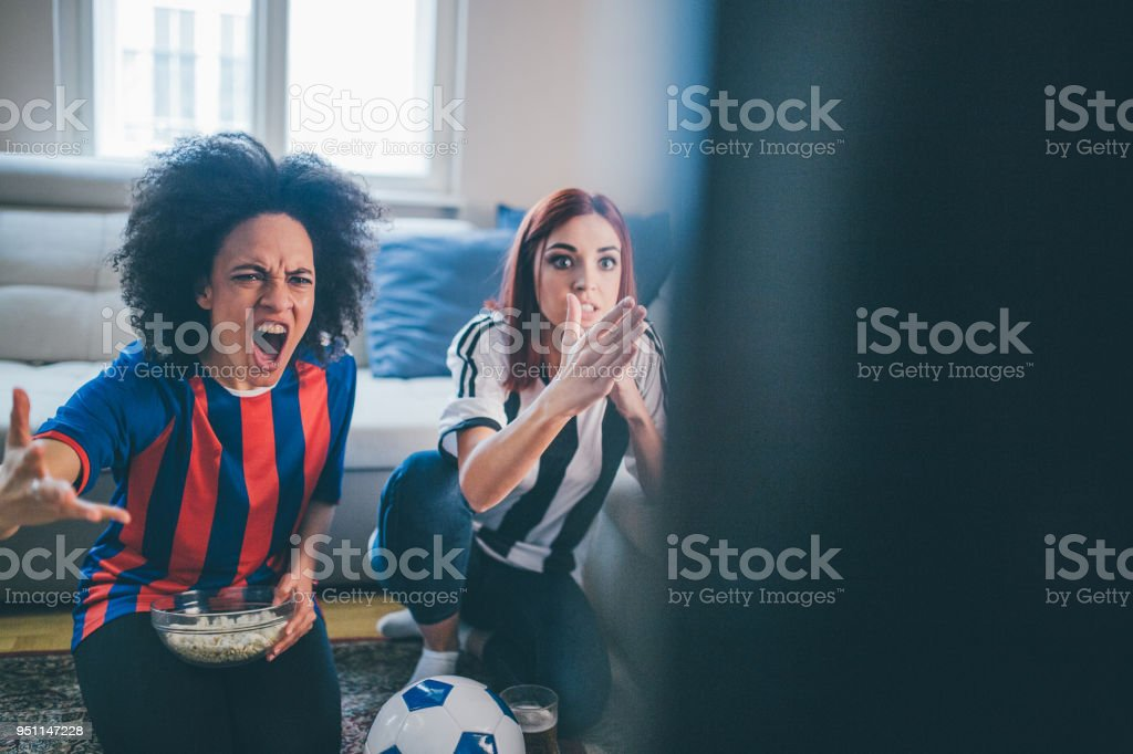 Women screaming and watching soccer game