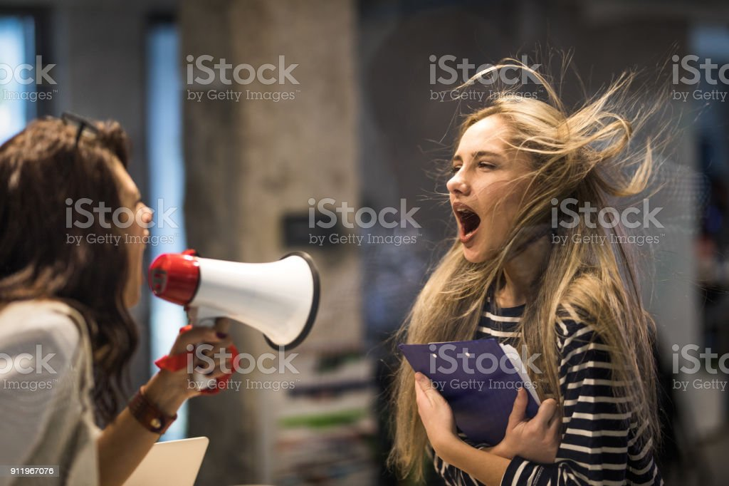 Angry female manager yelling at her colleague through megaphone. stock photo
