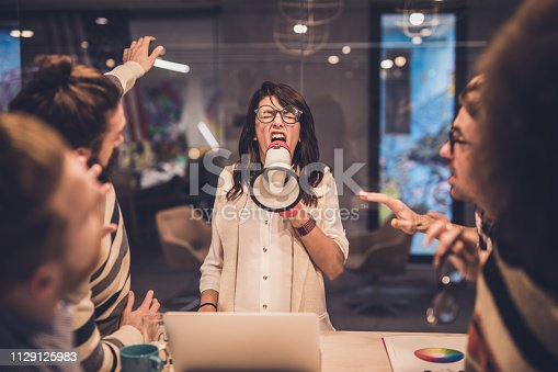 463813207 istock photo Angry female manager yelling at her colleagues through megaphone in the office. 1129125983