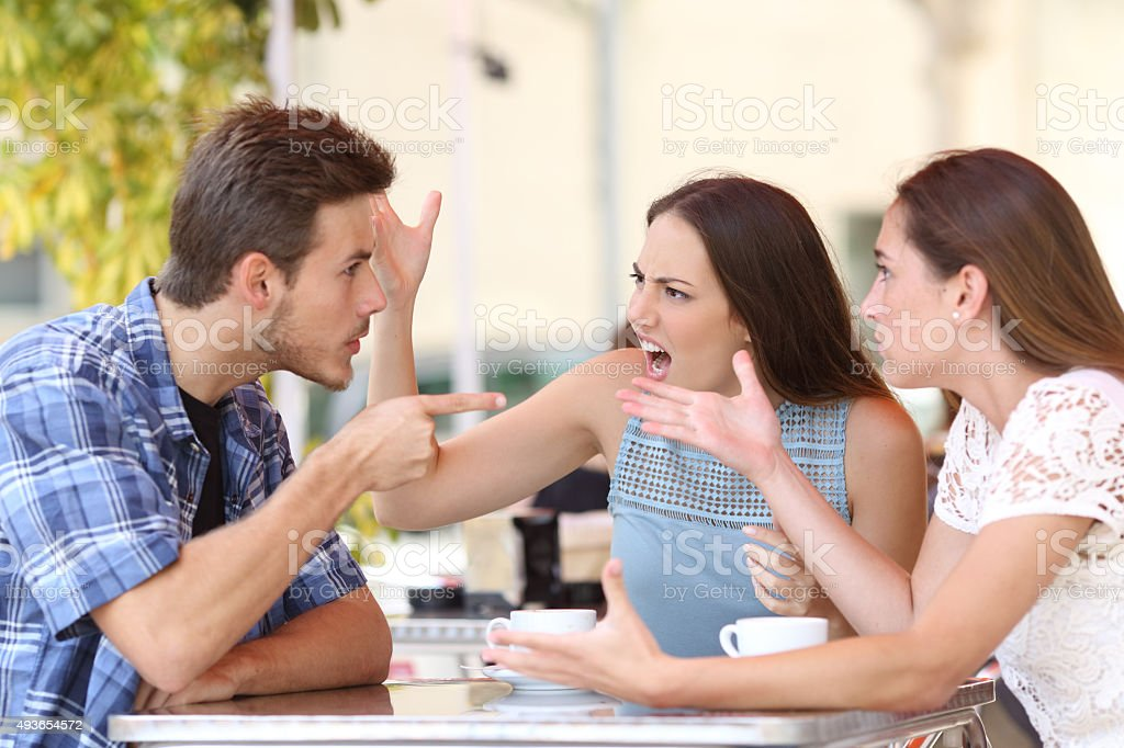 Angry friends arguing in a coffee shop stock photo