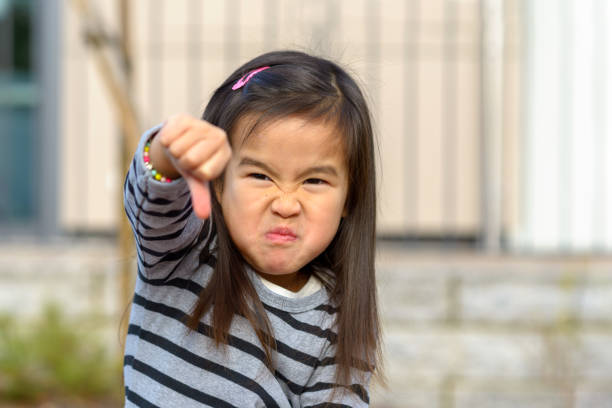 Angry frustrated girl throwing a temper tantrum stock photo