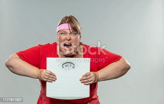 Overweight young woman having a hard fitness time with weight scale in her hands and a measuring tape around her neck. Set against a grey background