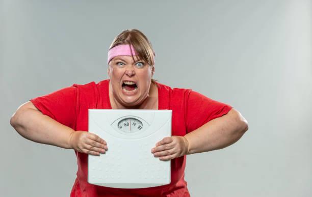 Wütende, frustrierte übergewichtige Frau mit Gewichtsskala – Foto