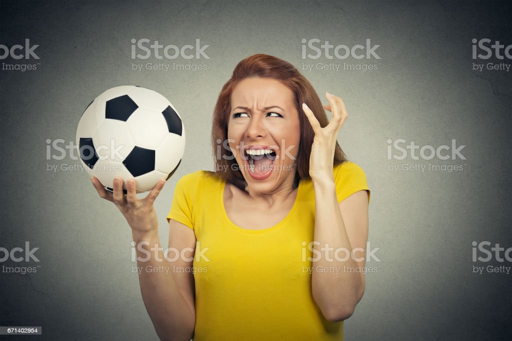 Angry frustrated woman screaming at soccer ball stock photo