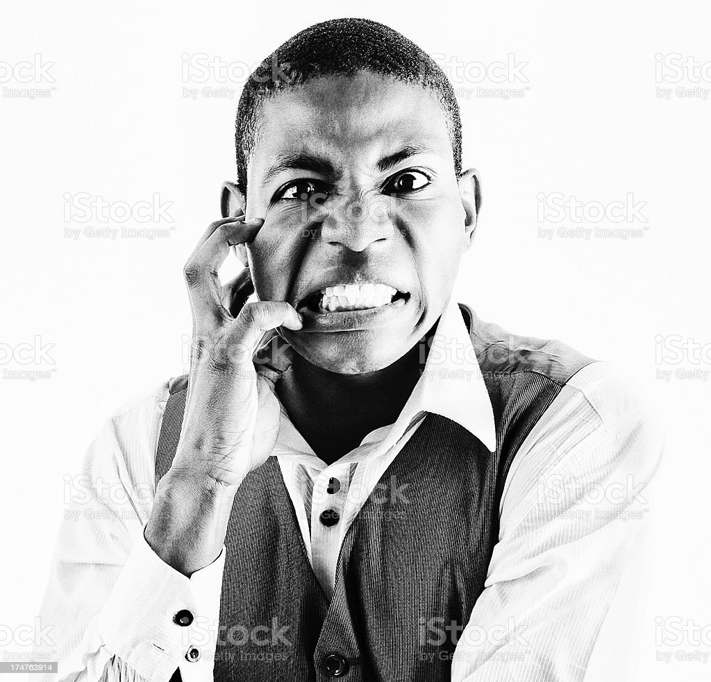 Angry frustrated young man grimaces and claws his face royalty-free stock photo