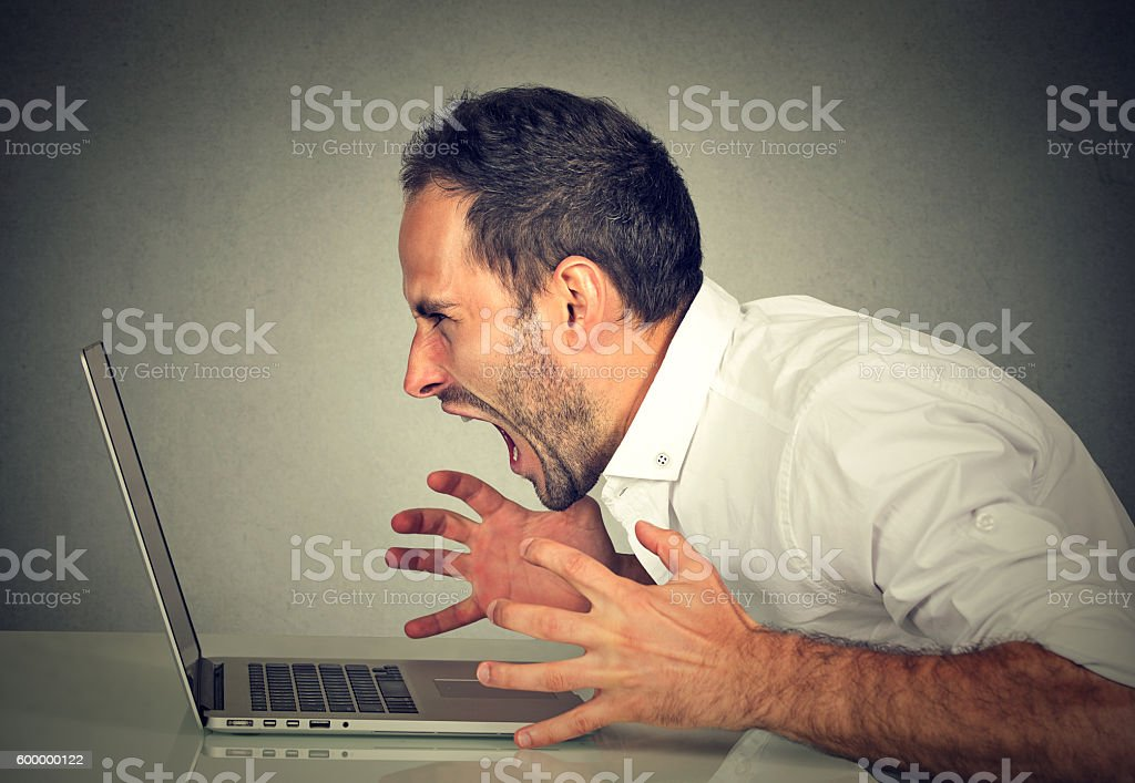 Angry furious business man screaming at computer stock photo