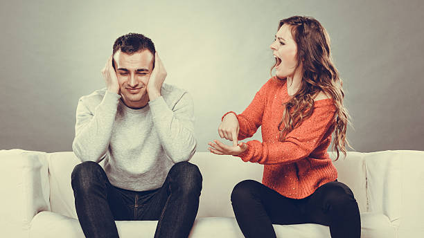 angry fury woman screaming man closes his ears. - man dominating woman stock photos and pictures