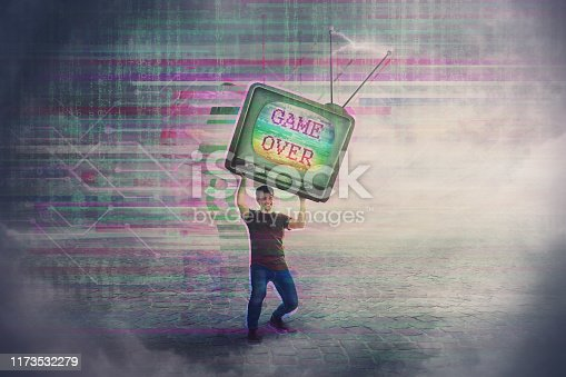 istock Angry gamer lifting up and throwing his old TV box after glitch text game over on the screen. Addicted, guy playing video games, lost in virtual reality world. Modern entertainment technology. 1173532279