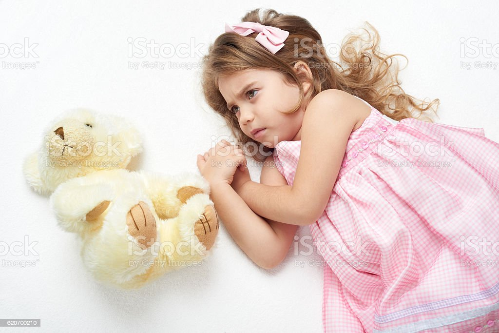 angry girl child with teddy bear lie on white towel stock photo