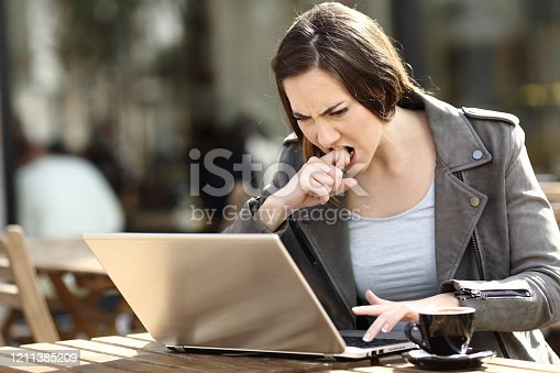 857213750 istock photo Angry girl frustrated using her laptop on a terrace 1211385209