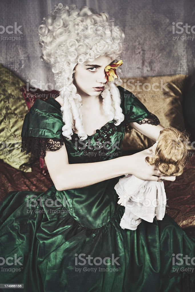 Angry Girl in Period Costume Chokes Her Doll stock photo