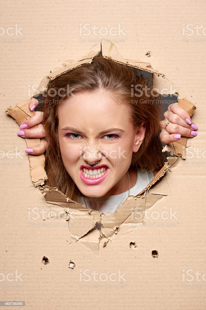 Angry girl peeping through hole in paper stock photo