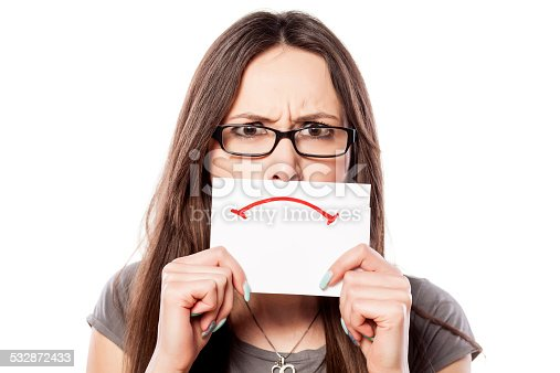 istock Angry girl with a sad smile drawn on paper 532872433